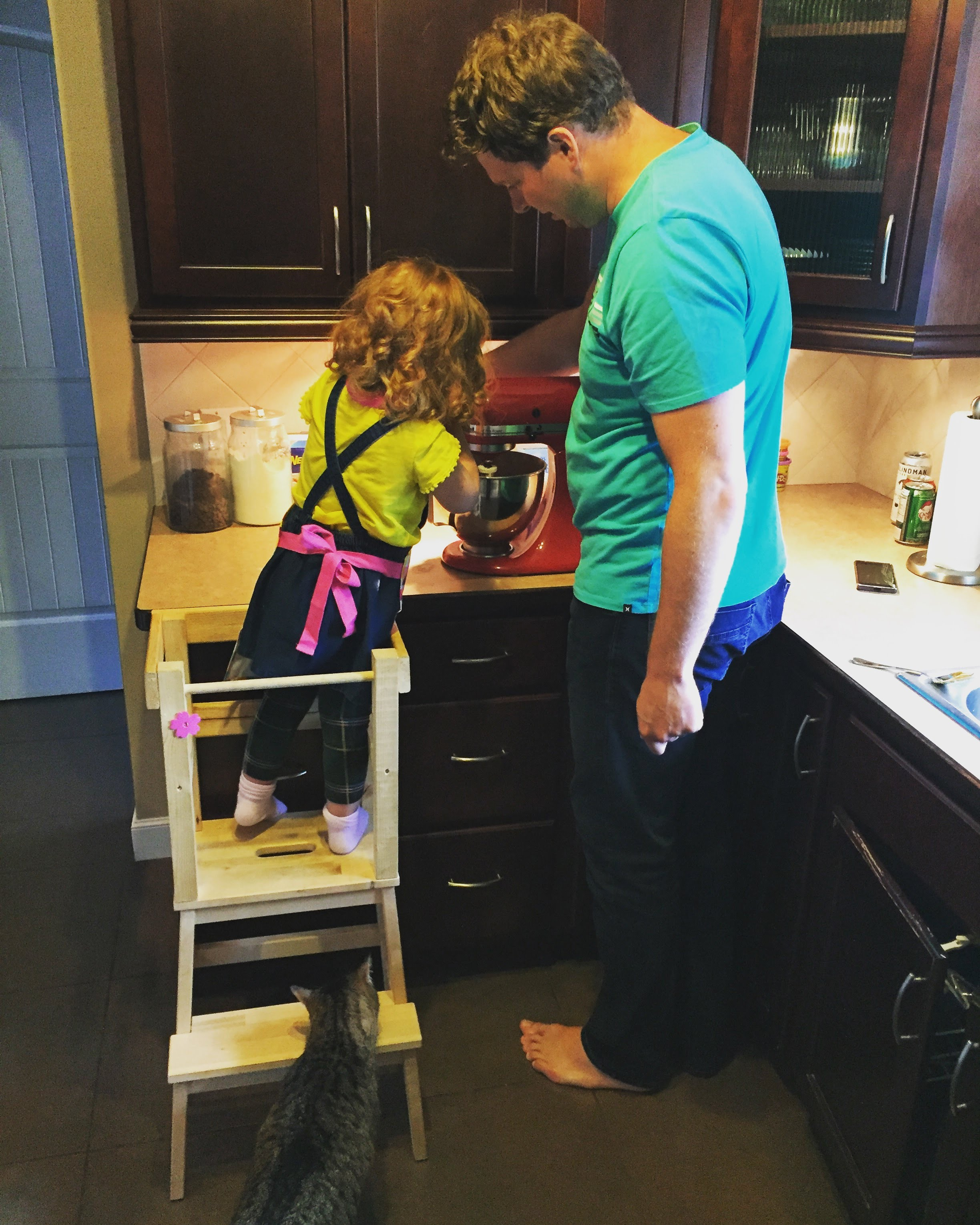 H helping dad make some cookies, with a sneak friend checking for crumbs.